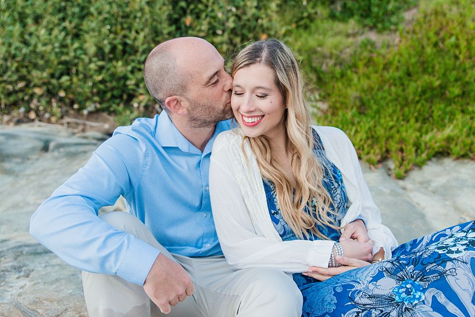 couple sitting and kissing san diego engagement photo inspiration
