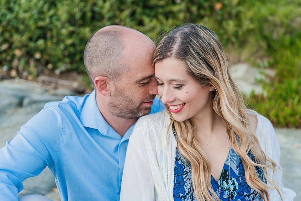 couple sitting and nuzzling close san diego engagement session