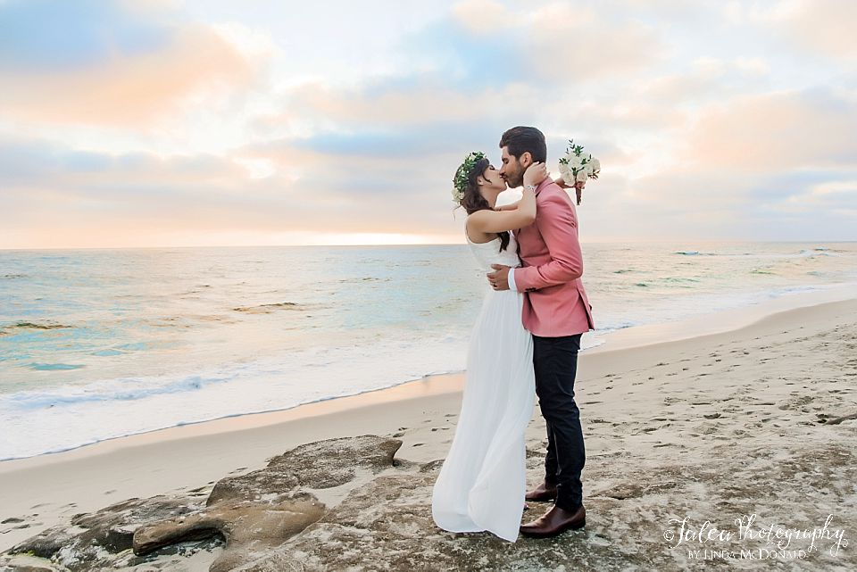 bride and groom kissing on rocks at windandsea beach san diego elopement