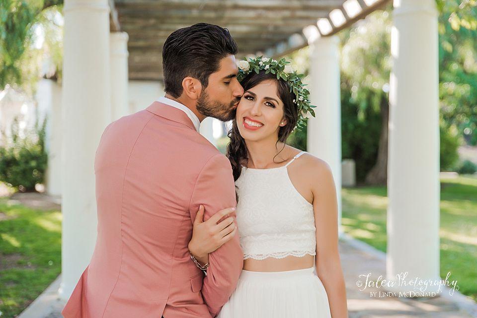 groom kissing brides cheek underneath arbor at Presidio Park San Diego