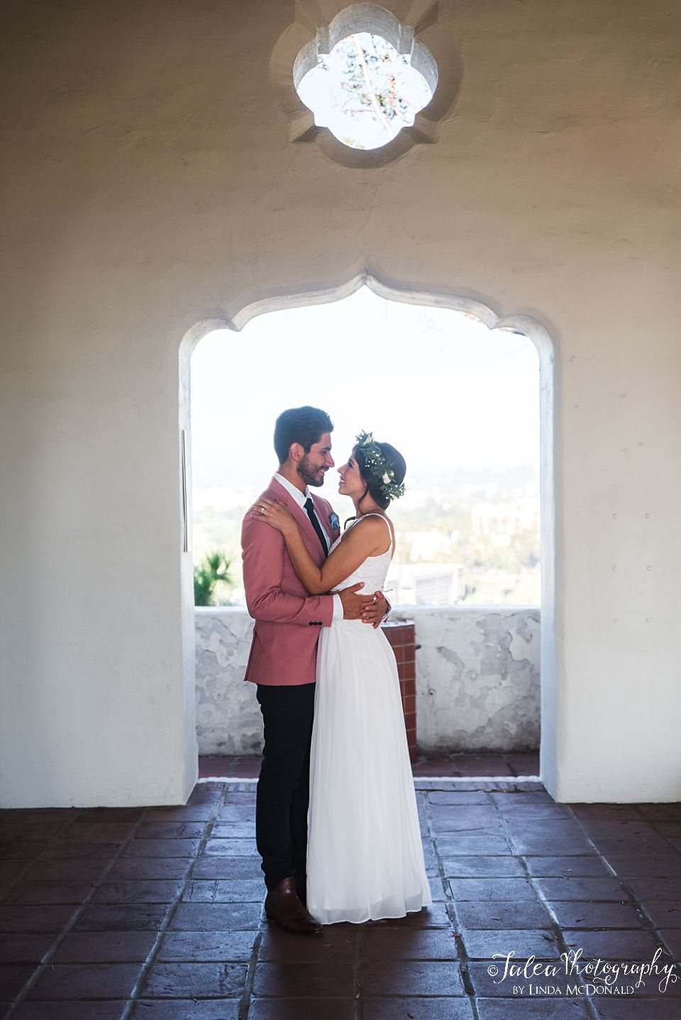 bride and groom standing in front of arch at Junipero Serra Museum San Diego