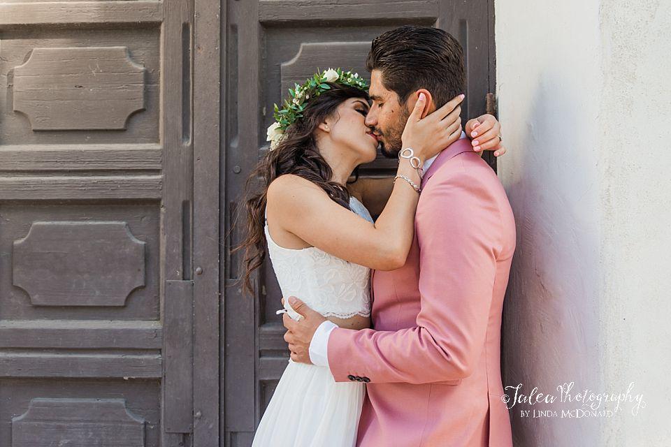 couple kissing in front of doorway at Junipero Serra Museum Old Town