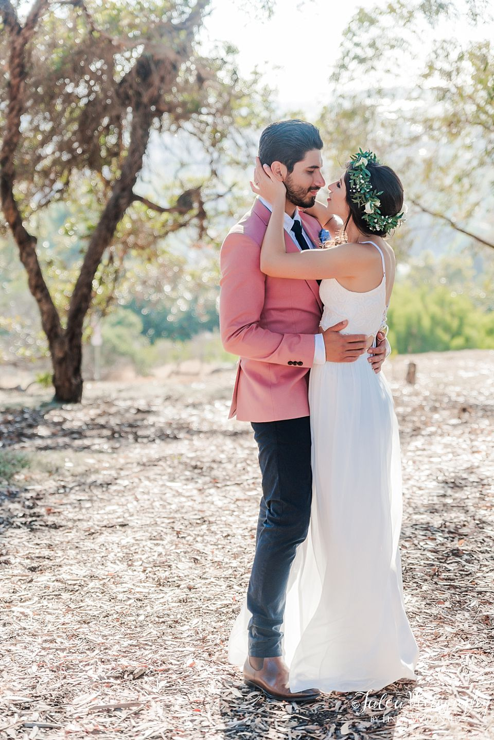 elopement couple with arms around each other rustic scenary