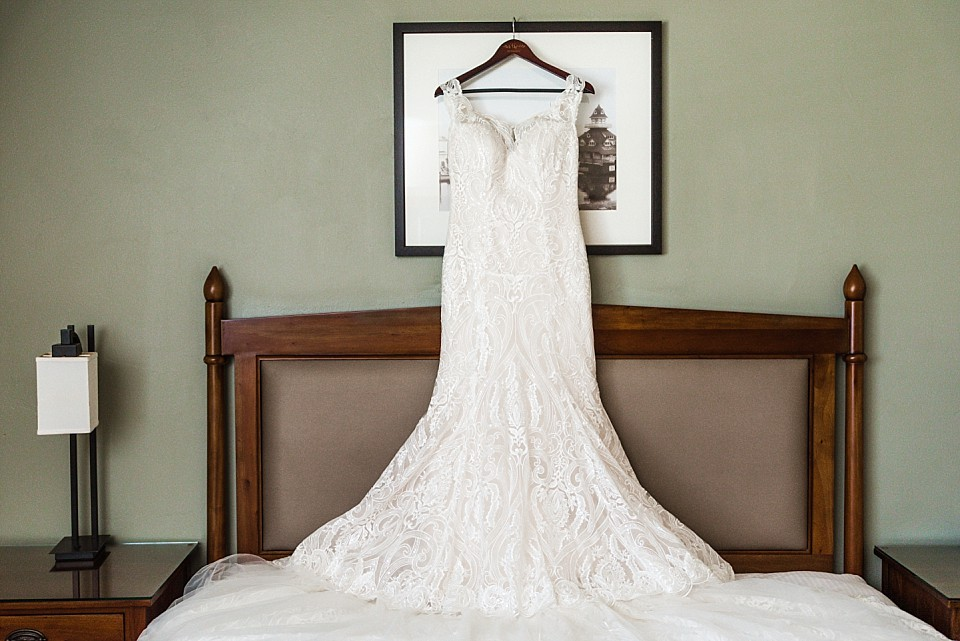 elegant classic style wedding dress hanging over bed Coronado hotel suite