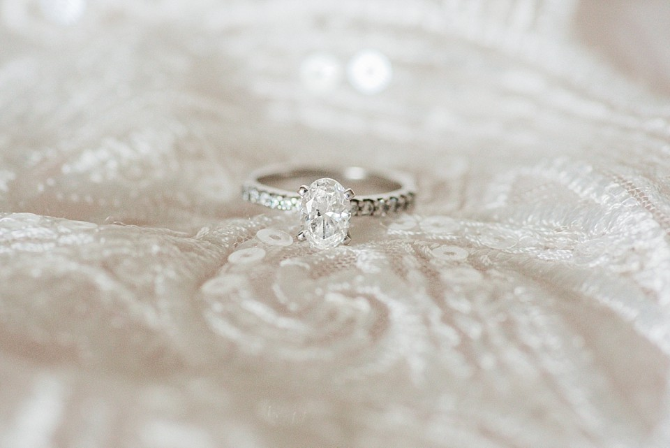 oval diamond wedding ring on top of lace wedding gown coronado wedding photographer