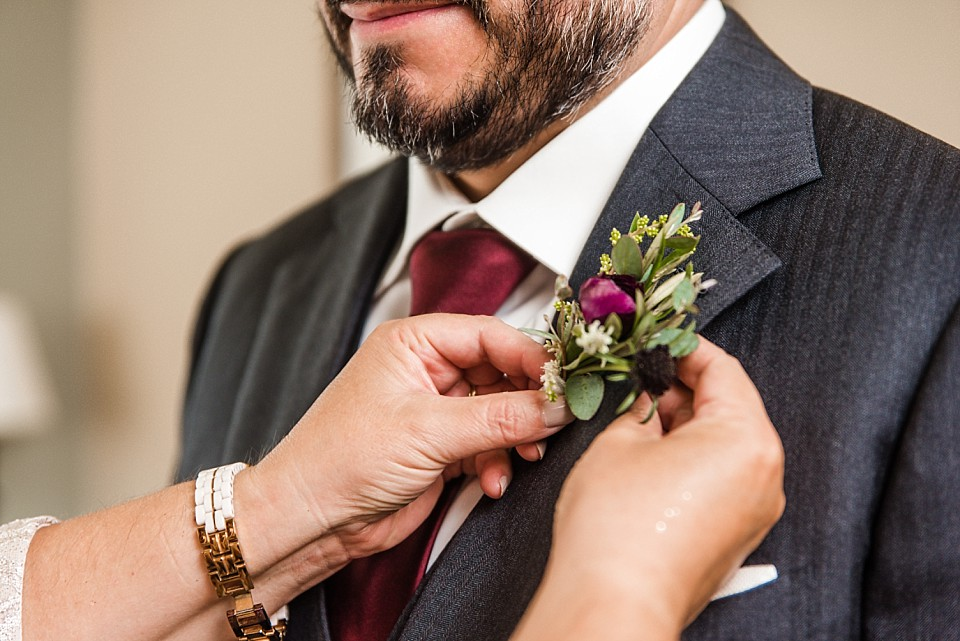 up close view of grooms mom pinning on boutonniere
