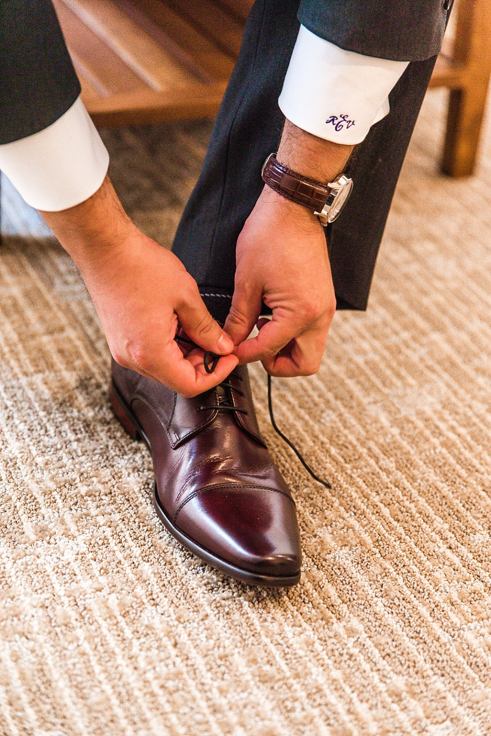 groom tying his shoe before the ceremony
