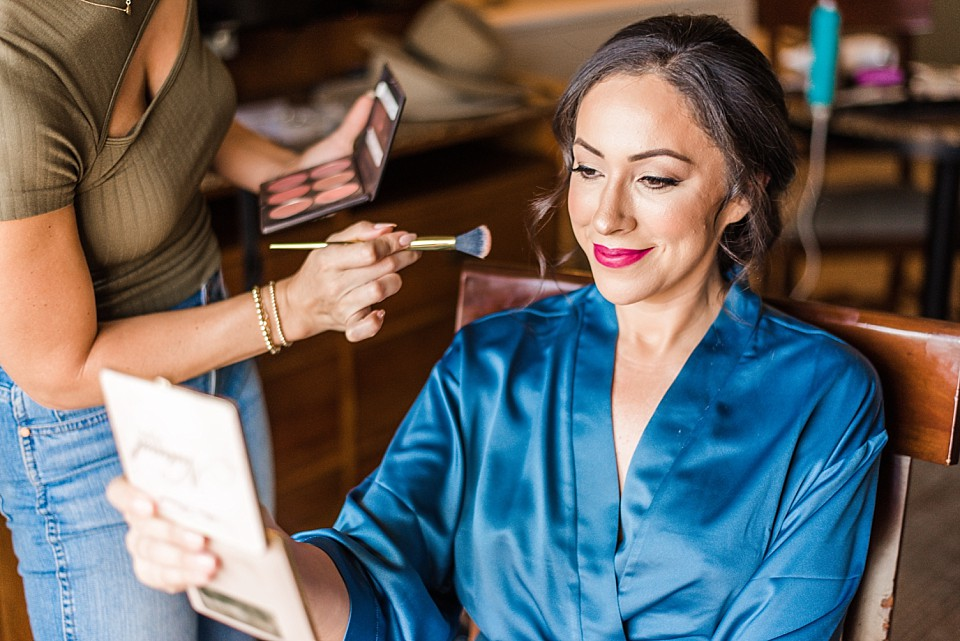 bride smiling mirror make up artist puts on finishing touches coronado hotel suite