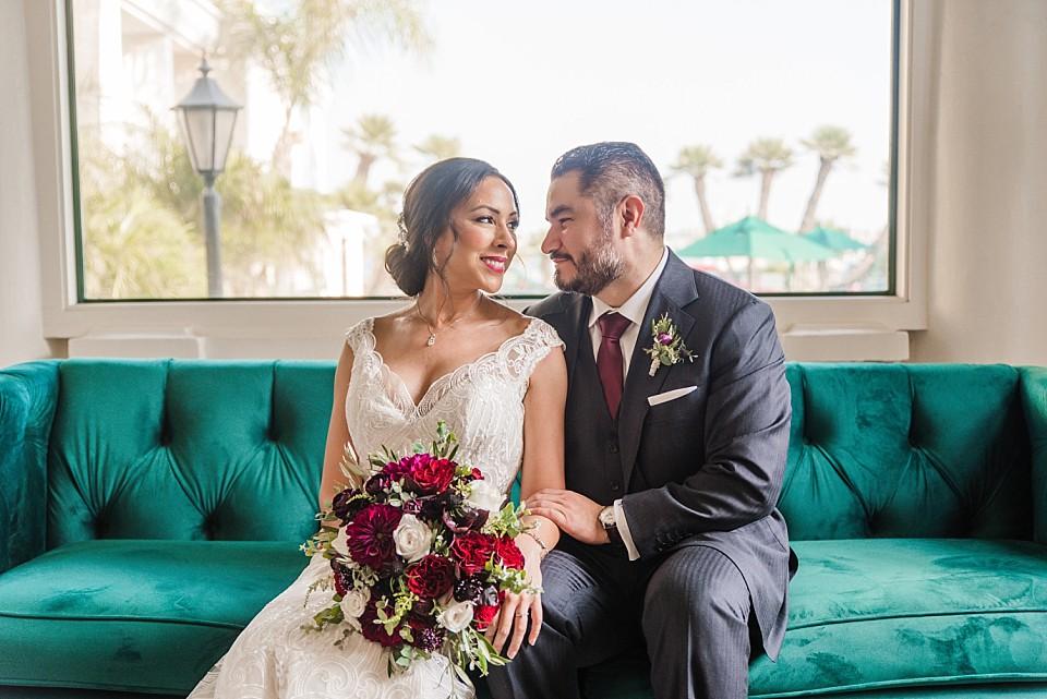 romantic couple portrait sitting green couch Coronado hotel