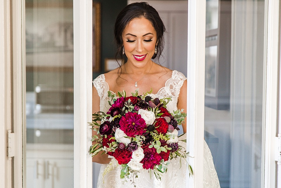 bride looks down brightly colored red white bridal bouquet Coronado wedding photographer