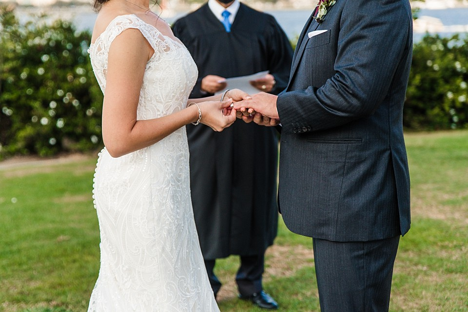 bride placing ring on grooms finger California wedding