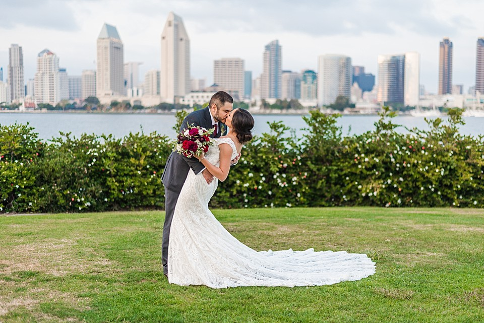 Coronado wedding ceremony groom dipping bride in front of San Diego skyline