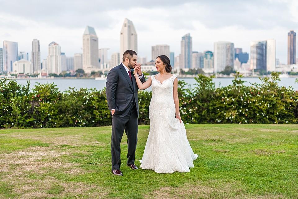 wide view of groom kissing brides hand Coronado outdoor wedding