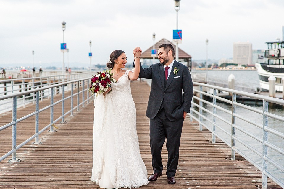 bride groom excitedly holding hands up at Coronado Ferry Landing