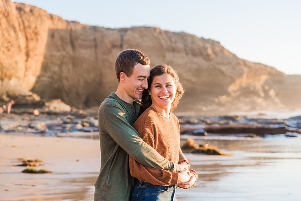 couple snuggling laughing sunset cliffs san diego engagement photos