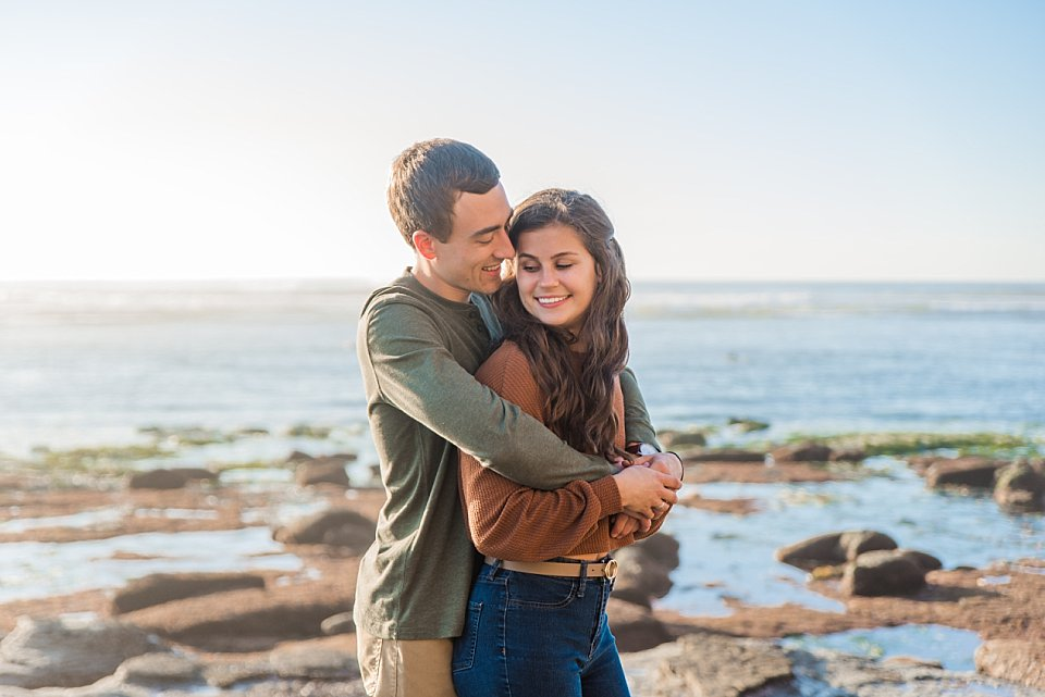 couple snuggling tightly engagement photos sunset cliffs
