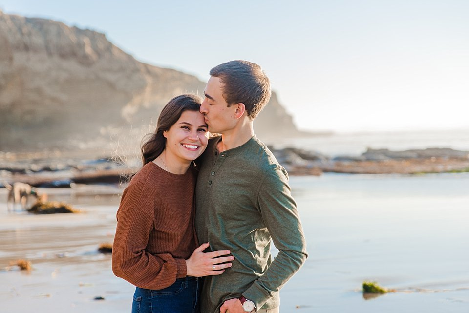 girl laughing while guy kisses her temple san diego engagement photoshootgirl laughing while guy kisses her temple san diegoengagement photoshoot