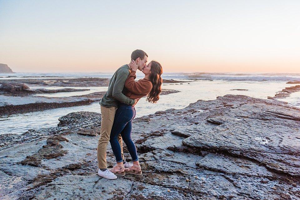 guy girl romantically dip kissing sunset cliffs engagement photos