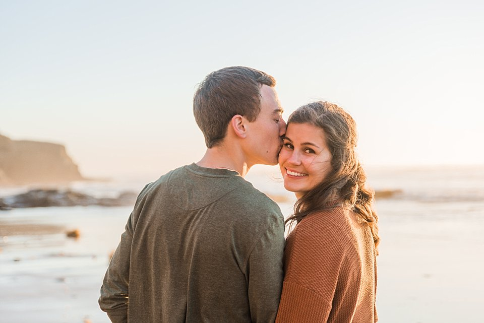 guy kissing girls temple while she is smiling san diego engagement photoshoot