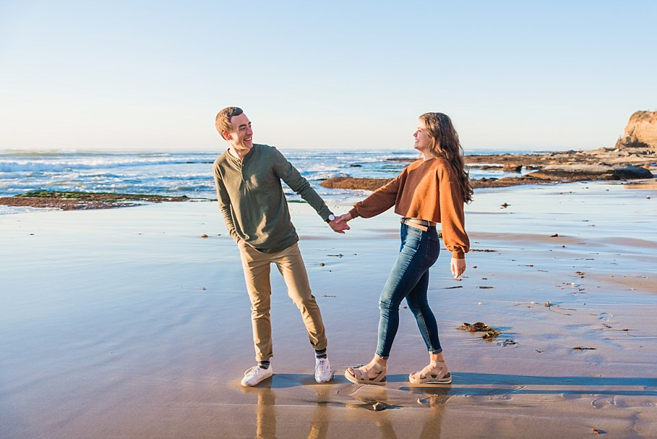guy pulling girl towards water san diego beach engagement photos